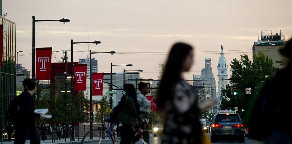 Temple students, flags, and Philadelphia skyline.